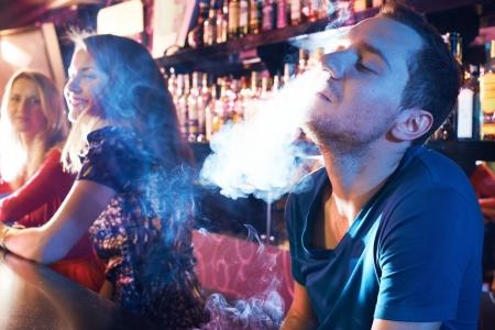 persona fumando: Retrato de hombre joven dejando que el humo de las fosas nasales, mientras que fumar pipa de agua