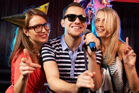 Portrait of happy friends singing in microphone in the karaoke bar  photo