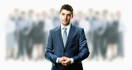 spokesperson: Creative image of attractive businessman in suit with crowd of people on background