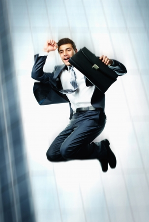 businessman jumping: Creative image of joyful businessman with briefcase jumping on background of skyscraper Stock Photo