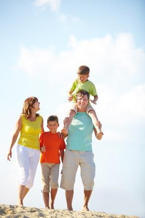 行き: 夏にはビーチを歩いて幸せな家族
