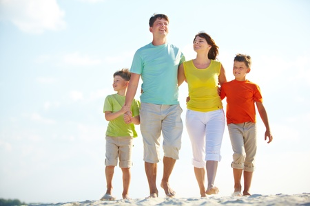 a happy family walking down the beach on summer photo