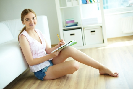 young girl barefoot: Pretty girl sitting on the floor and looking at camera while doing homework Stock Photo