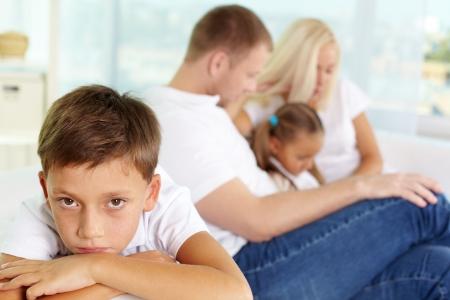 fille triste: Portrait d'un gar�on triste sur fond de ses parents et sa soeur