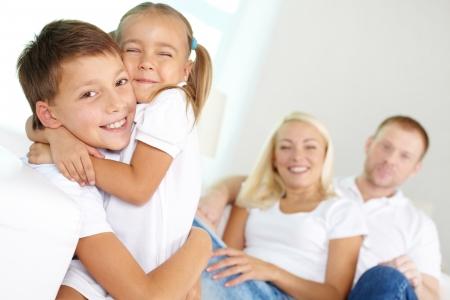 padres e hijos felices: Retrato de niños felices que abrazan con los padres sentados detrás