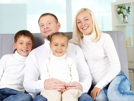 pullovers: Portrait of happy family in white pullovers looking at camera