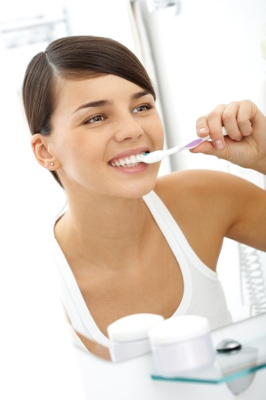 Image of pretty female brushing her teeth in front of mirror in the morning photo