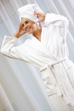 pureness: Portrait of pretty female in white bathrobe with towel on head Stock Photo