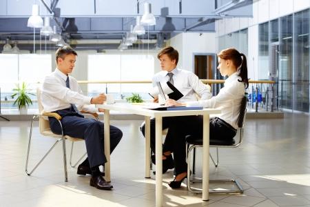 hombre sentado: Grupo de socios de trabajo, interactuando en la reunión