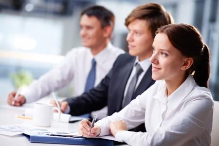 entrevista de trabajo: Tres hombres de negocios que se sientan en el seminario, la atención se centra en la mujer