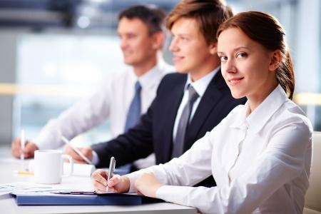 Drei Geschäftsleute sitzen am Seminar mit lächelnden Frau in Vordergrund Standard-Bild