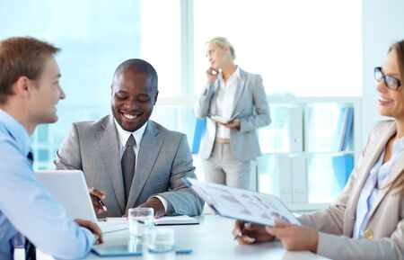 Portrait of confident boss smiling while his partners interacting at meeting photo