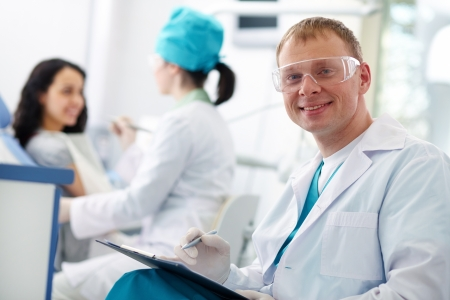 stomatological: Smiling doctor in protective eyewear looking at camera