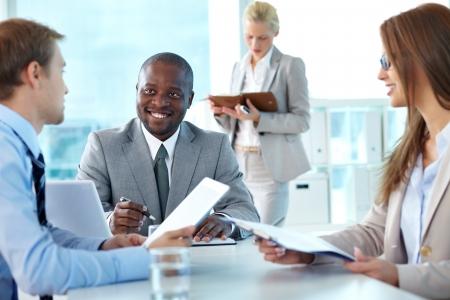 grupos de personas: Retrato de la protuberancia confidente que sonr�e al interactuar con los empleados a satisfacer