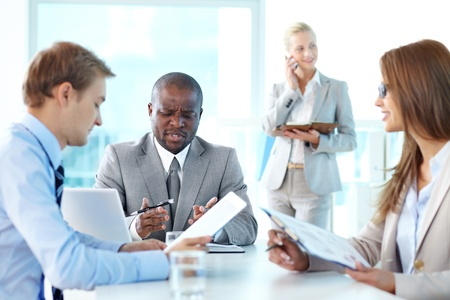 Portrait of frowning boss looking at document with his two employees sitting near by Stock Photo - 15315942