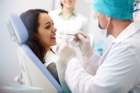 male dentist: Pretty girl sitting at the dentist�s and having mouth checkup