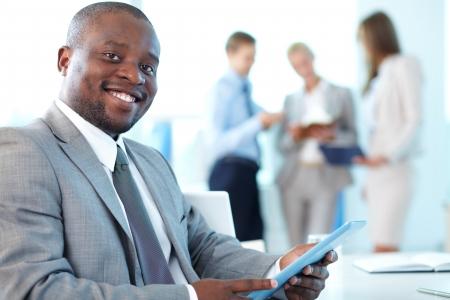 Portret van gelukkige leider met touchpad kijken camera in werkomgeving