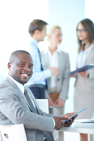 Portrait of happy leader with touchpad looking at camera in working environment Stock Photo - 15315967