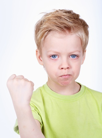 frowned: Cute little boy threatening at camera with a fist Stock Photo