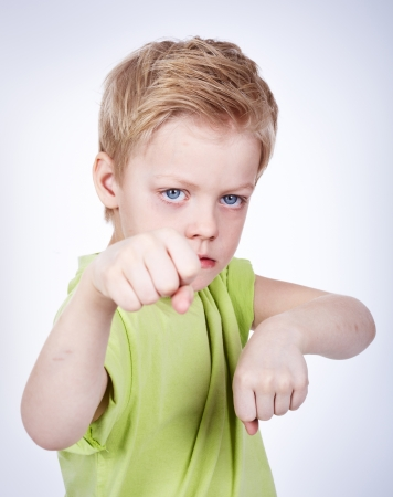 Cute little boy ready to fight someone photo