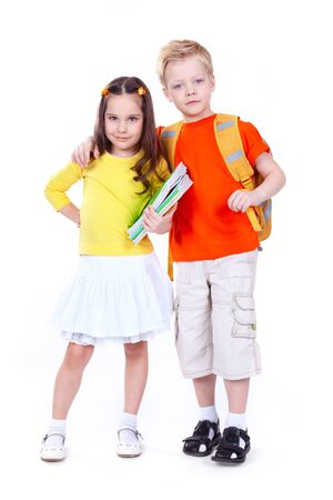 Two school children isolated on white background looking confidently at camera photo
