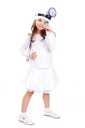 enfermera con cofia: Niña linda vestida como un médico que mira la cámara con una sonrisa alegre