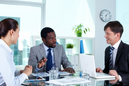 Portrait of three businesspeople interacting in office Stock Photo - 15315943