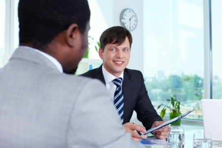 Portrait of confident businessman looking at employee photo