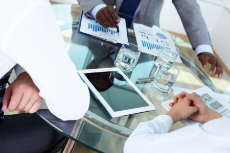 Close-up of workplace with hands of business partners over it Stock Photo - 15315953