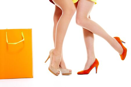 Female legs over white background with paperbag near by photo