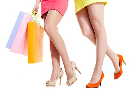 Female legs over white background with paperbags in hands photo