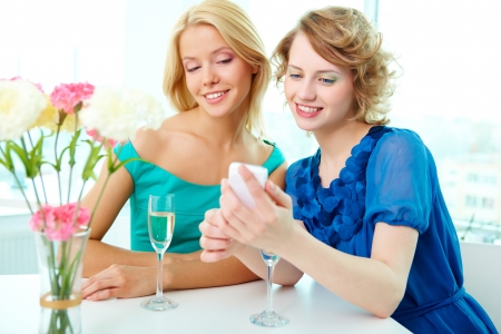 Pretty girls looking through images in cellular phone photo