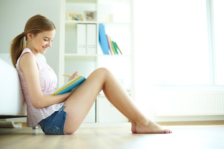 piedi nudi di bambine: Bella ragazza seduta sul pavimento e fare i compiti