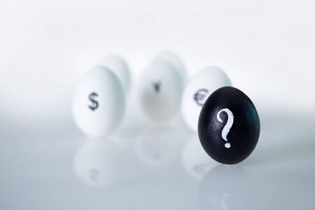 Image of black egg with question mark with group of eggs on background photo