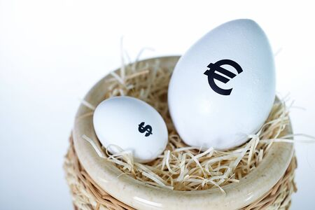 Image of big egg with euro sign and smaller one with dollar sign in nest photo