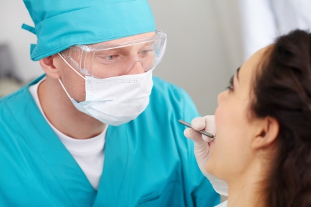 oral hygiene: Male dentist in protective uniform carrying out mouth checkup