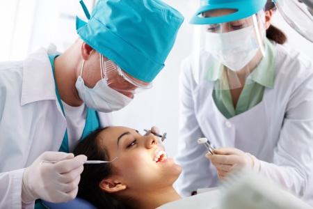 higiene bucal: Pretty paciente con el tratamiento oral en la clínica dental