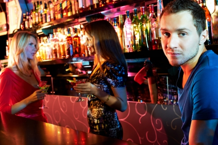 woman bar: Portrait cute guy looking at camera at party with two girls chatting on background