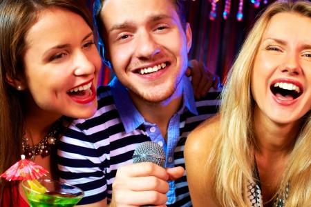 Portrait of happy people singing in microphone in the karaoke bar  photo