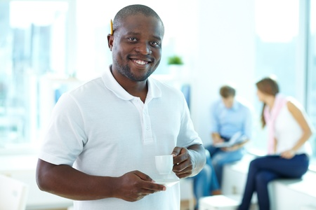Portrait of happy African guy with cup looking at camera in working environment Stock Photo - 15436188
