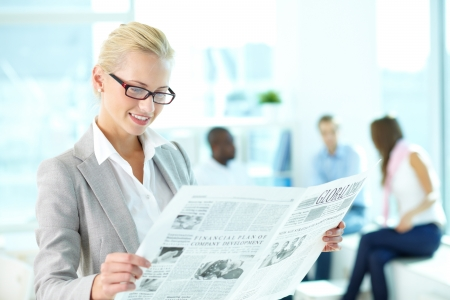 newspaper reading: Portrait of happy female reading newspaper in working environment