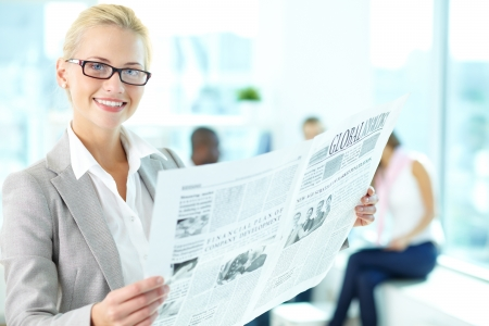 discussing: Portrait of happy female with newspaper looking at camera in working environment