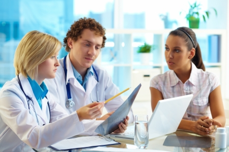 healthcare and medicine: Pretty patient listening to therapeutists at medical consultation
