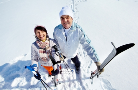Portrait of happy mature couple of skiers looking at camera and laughing photo