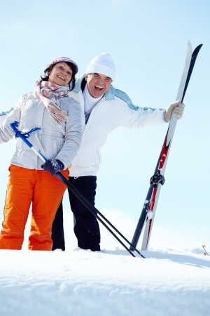 Portrait of happy mature couple of skiers laughing photo