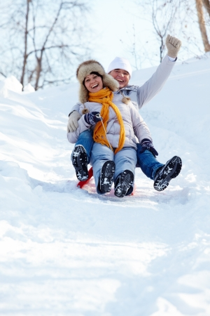 winter fashion: Portrait of happy mature couple riding on sledge in winter Stock Photo