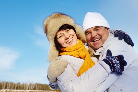 Portrait of happy mature couple in winter clothes looking at camera outside photo