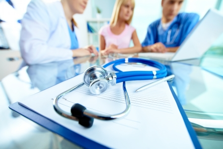 doctors tool: Close-up of stethoscope and paper on background of doctors and patient working with laptop Stock Photo