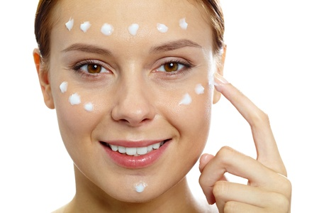 purifying: Fresh woman applying hydrating cream onto her face Stock Photo