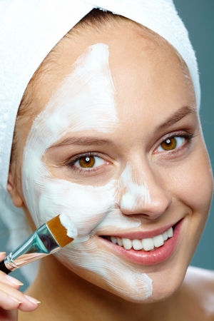 Fresh woman applying facial mask onto her face with brush photo